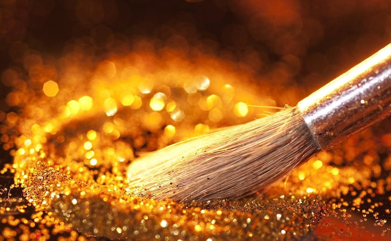 Pincel numa mesa metálica espalhando glitter dourado